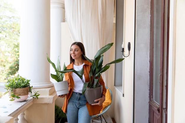 Średnio strzał kobieta niosąca rośliny