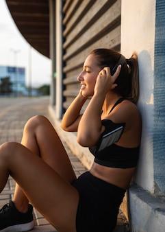 Średnio strzał kobieta nosi słuchawki