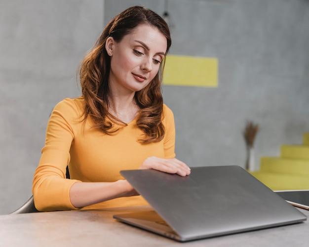 Średnio strzał kobieta otwierająca laptopa