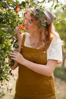 Średnio strzał kobieta pachnący kwiat