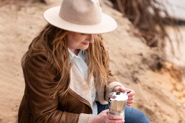 Średnio strzał kobieta parzenia kawy na zewnątrz