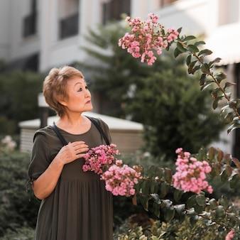 Średnio strzał kobieta patrząc na kwiaty