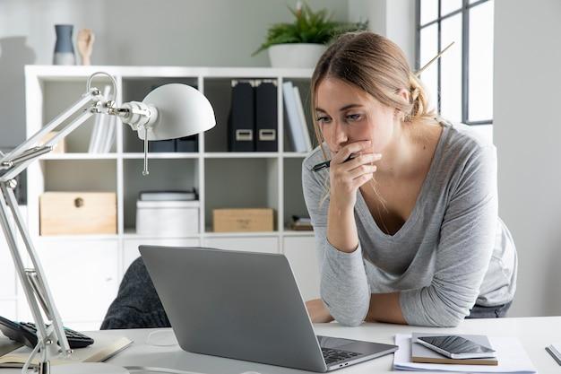 Średnio strzał kobieta patrząc na laptopa