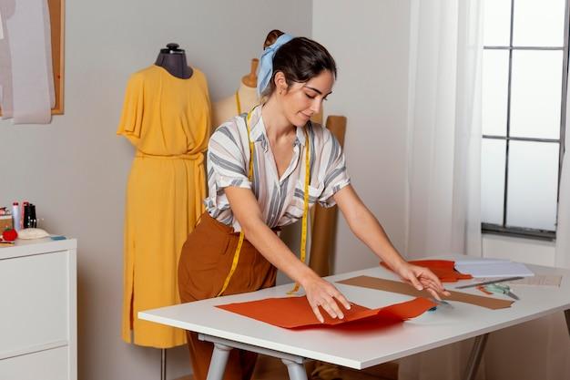Średnio strzał kobieta patrząc na tkaninę