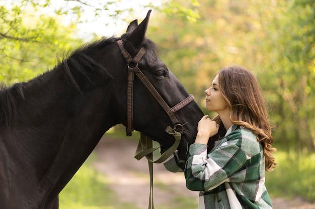 Średnio strzał kobieta pieszcząca słodkiego konia