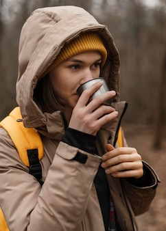 Średnio strzał kobieta pije z kubka