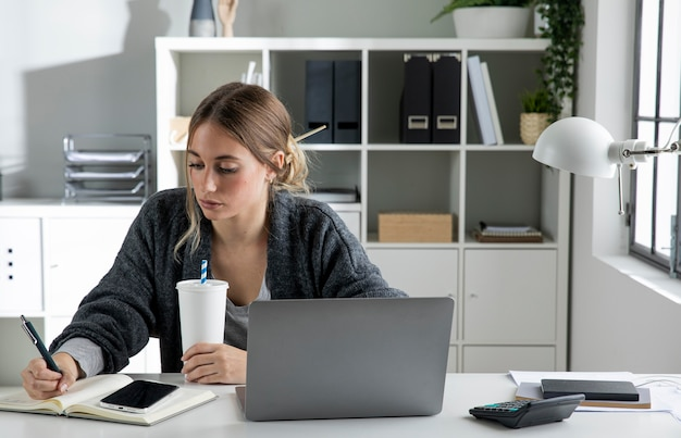 Średnio strzał kobieta pisze na notebooku