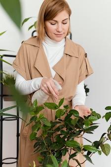 Średnio strzał kobieta podlewania roślin liści