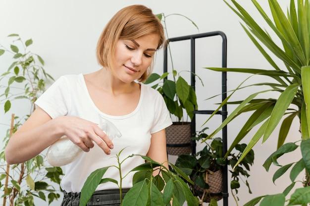 Średnio strzał kobieta podlewania roślin