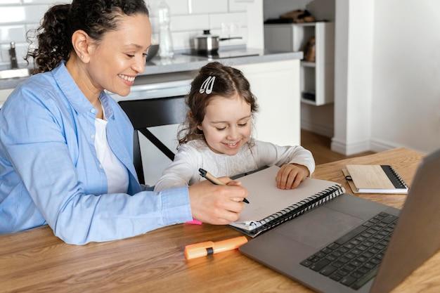 Średnio strzał kobieta pomaga dziewczynie w odrabianiu prac domowych