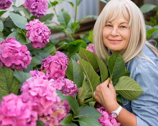 Średnio strzał kobieta pozująca blisko kwiatów