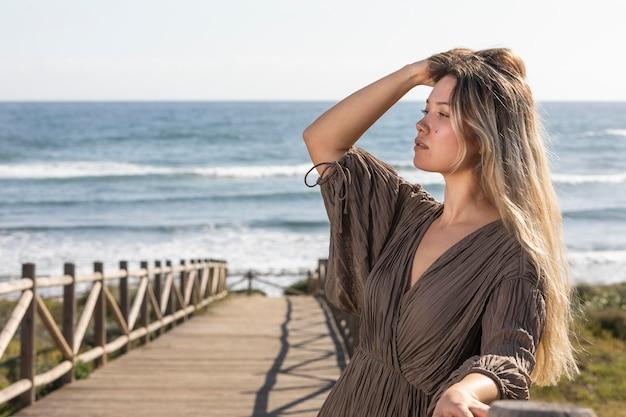 Średnio strzał kobieta pozuje nad morzem