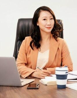 Średnio strzał kobieta pozuje przy biurku