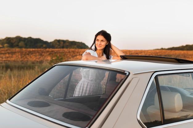 Średnio strzał kobieta pozuje w pobliżu samochodu