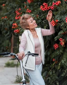 Średnio strzał kobieta pozuje z kwiatami