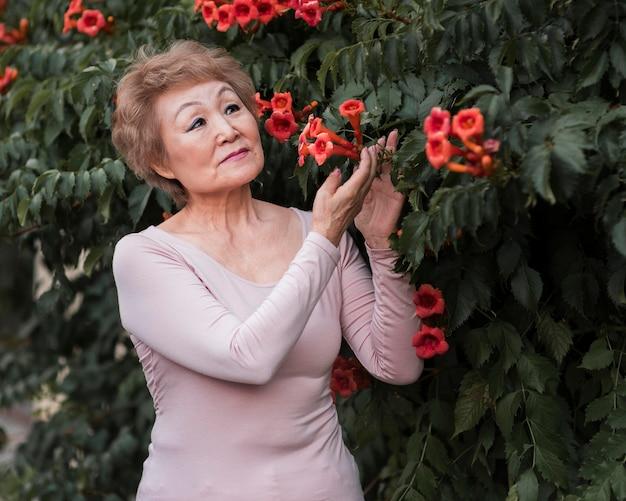 Średnio strzał kobieta pozuje z pięknymi kwiatami