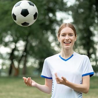 Średnio strzał kobieta pozuje z piłką
