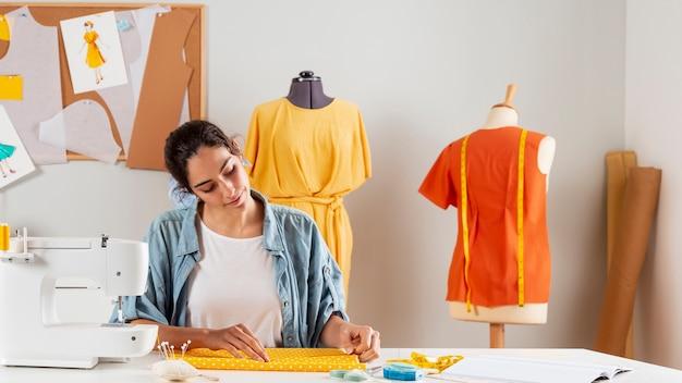 Średnio strzał kobieta pracująca z tkaniną