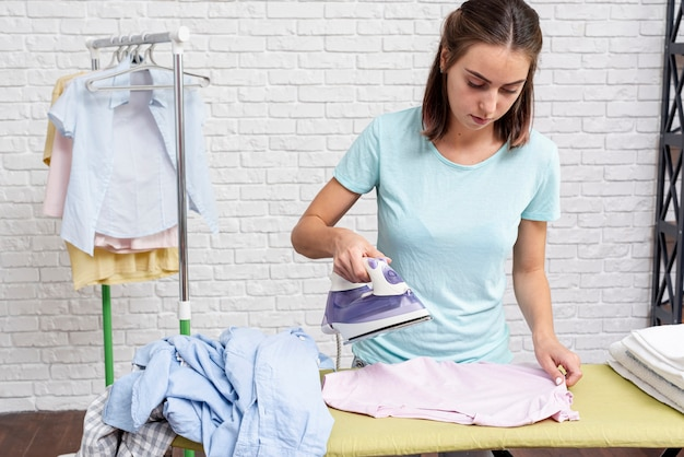 Średnio strzał kobieta prasowania odzieży w pomieszczeniu