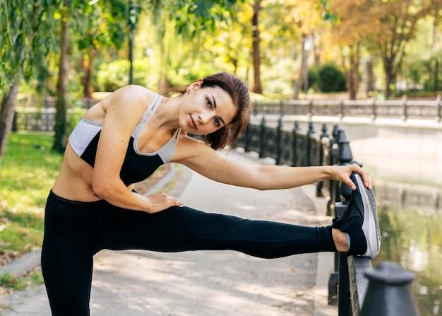 Średnio Strzał Kobieta Rozciągająca Nogę Premium Zdjęcia