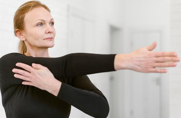 Średnio strzał kobieta rozciągająca ramię