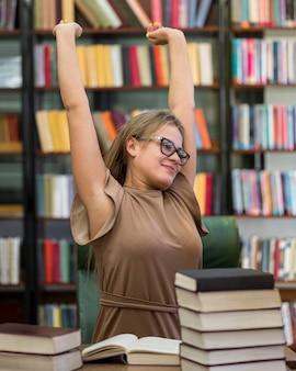 Średnio strzał kobieta rozciągająca się w bibliotece