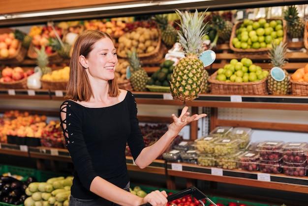 Średnio strzał kobieta rzuca ananasa w powietrzu