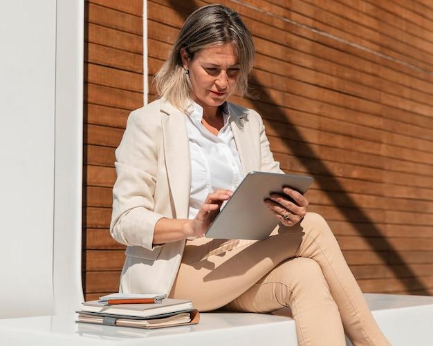 Średnio strzał kobieta siedząca i pracująca