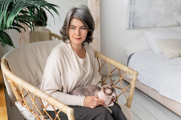 Średnio strzał kobieta siedząca z kotem