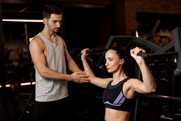 Średnio strzał kobieta trenująca na siłowni