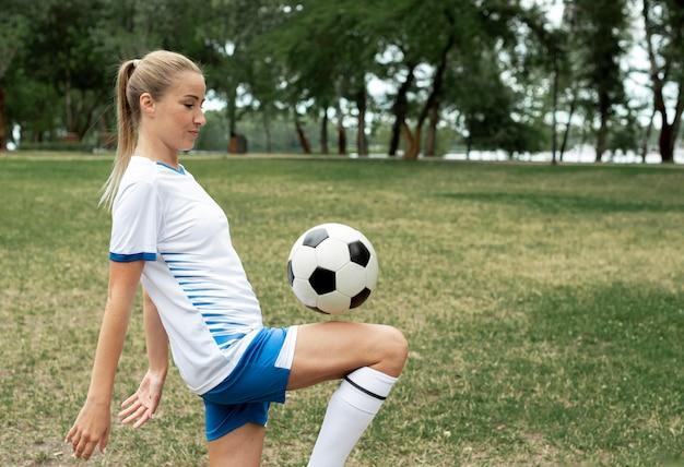 Średnio strzał kobieta trenująca z piłką