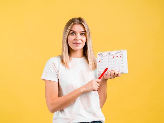 Średnio strzał kobieta trzyma długopis i okres kalendarza