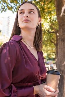 Średnio strzał kobieta trzyma filiżankę kawy
