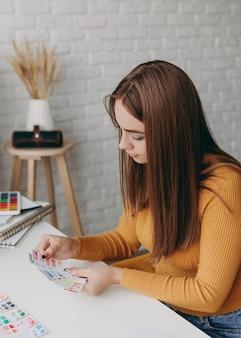 Średnio strzał kobieta trzyma karty palety kolorów