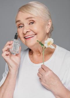 Średnio strzał kobieta trzyma kwiat i butelkę
