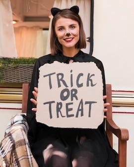Średnio strzał kobieta trzyma znak halloween