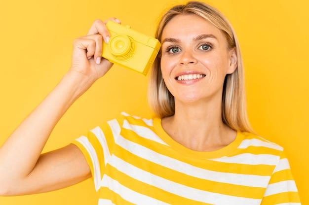 Średnio strzał kobieta trzyma żółtą kamerę