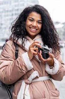 Średnio strzał kobieta trzymając aparat