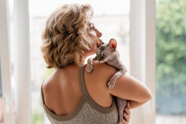 Średnio strzał kobieta trzymająca bezwłosego kota