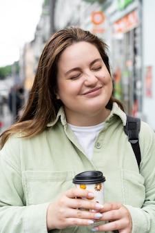 Średnio strzał kobieta trzymająca filiżankę kawy