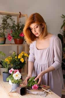 Średnio strzał kobieta trzymająca kwiat