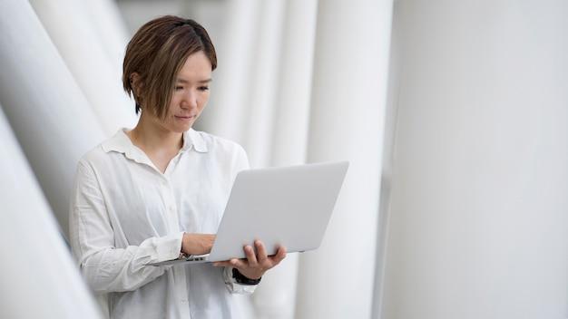 Średnio strzał kobieta trzymająca laptopa