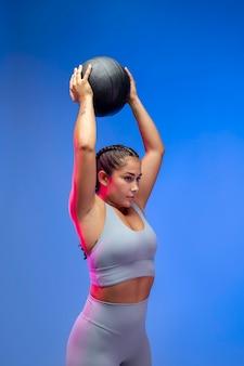 Średnio strzał kobieta trzymająca piłkę w górę