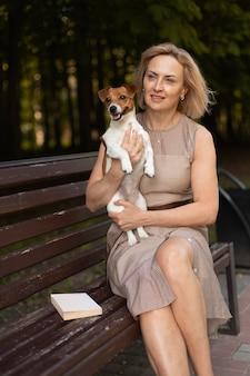Średnio strzał kobieta trzymająca psa na zewnątrz