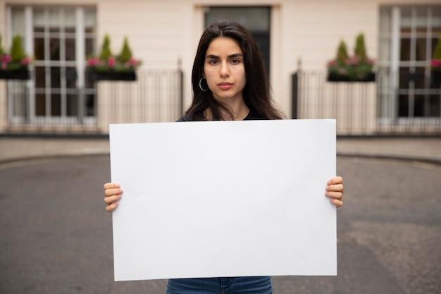 Średnio strzał kobieta trzymająca pustą tabliczkę