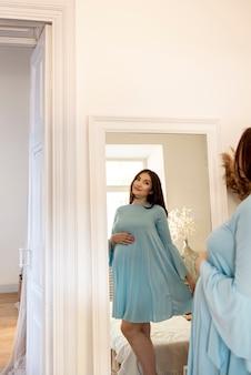 Średnio strzał kobieta w ciąży patrząc w lustro