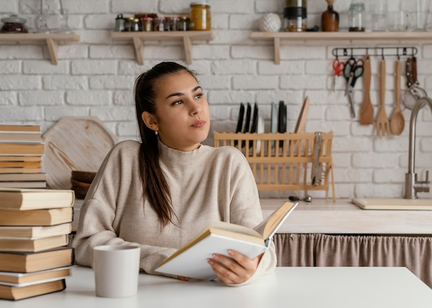 Średnio strzał kobieta w czytaniu w kuchni