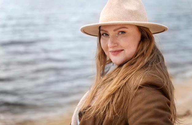 Średnio strzał kobieta w kapeluszu nad morzem