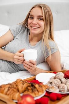 Średnio strzał kobieta w łóżku z filiżanką kawy