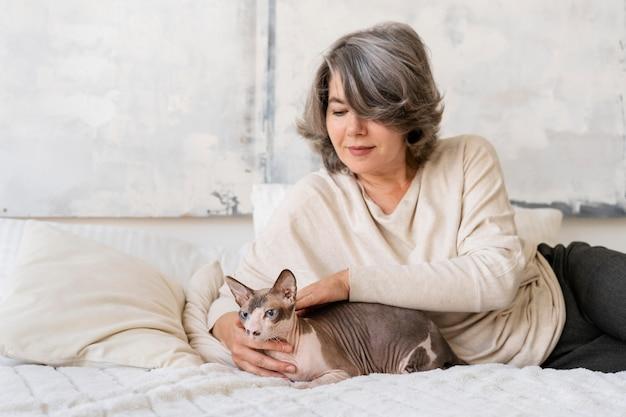 Średnio strzał kobieta w łóżku z kotem